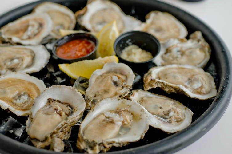 un plat d'huîtres servies avec des sauces et du citron